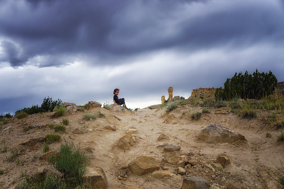 Boy rests on trail to chimney rock, Ghost Ranch, New Mexico